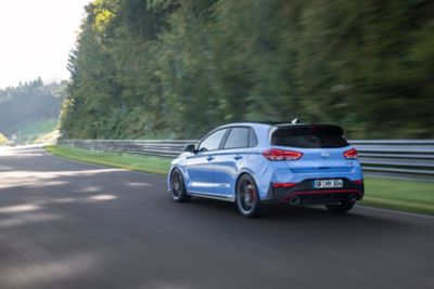 Rearview of the new Hyundai i30 N driving on a race track.