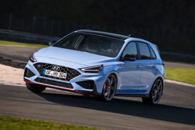 The new Hyundai i30 N on a race track, slicing a curve.