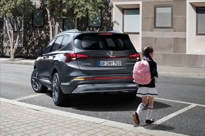 The new Hyundai SANTA FE 7 seat SUV from the back, with a school girl crossing behind the car.
