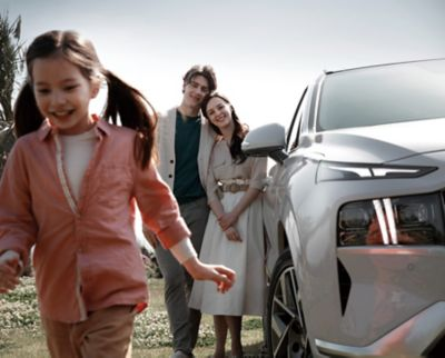 A family standing next to the new SANTA FE 7 seat SUV in white.