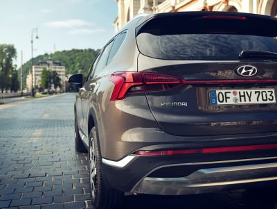 The new Hyundai SANTA FE 7 seat SUV pictured from the rear driving down a road.